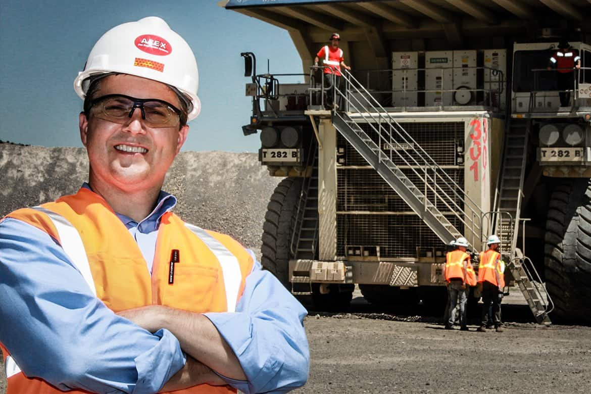 Owner Rod Cavallero posing in front of a mining vehicle wearing a safety vest and AFEX hard hat