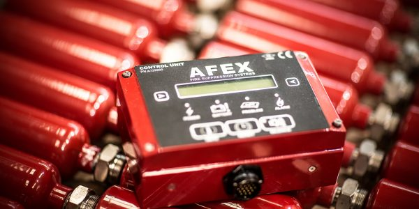 AFEX Control Unit laying on top of small fire suppression tanks