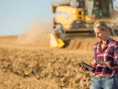 female farmer standing in wheat field while checking the data on combine harvester behind her. Telematics, agriculture, harvesting heavy equipment, combines, agriculture industry