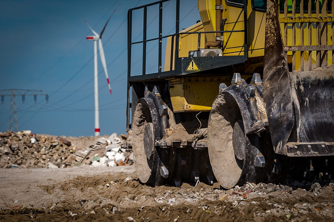 trash compactor vehicle in landfill compacting waste
