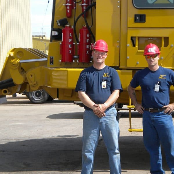 Two construction workers standing in front of their CAT truck with AFEX fire suppression systems installed